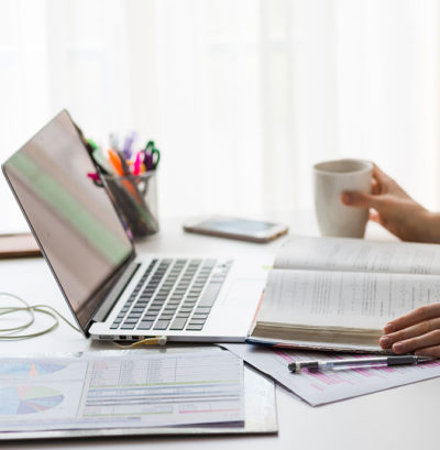 Open laptop on desk with open textbook holding cup of coffee