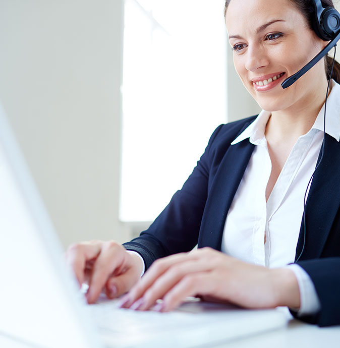 Woman in headset typing on computer