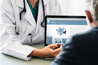 doctor showing results to a patient on laptop. medical billing