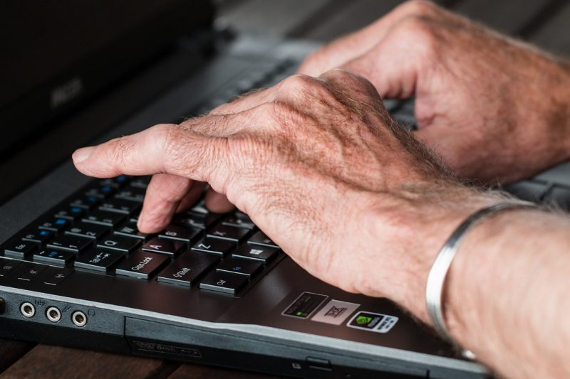 old man hands typing